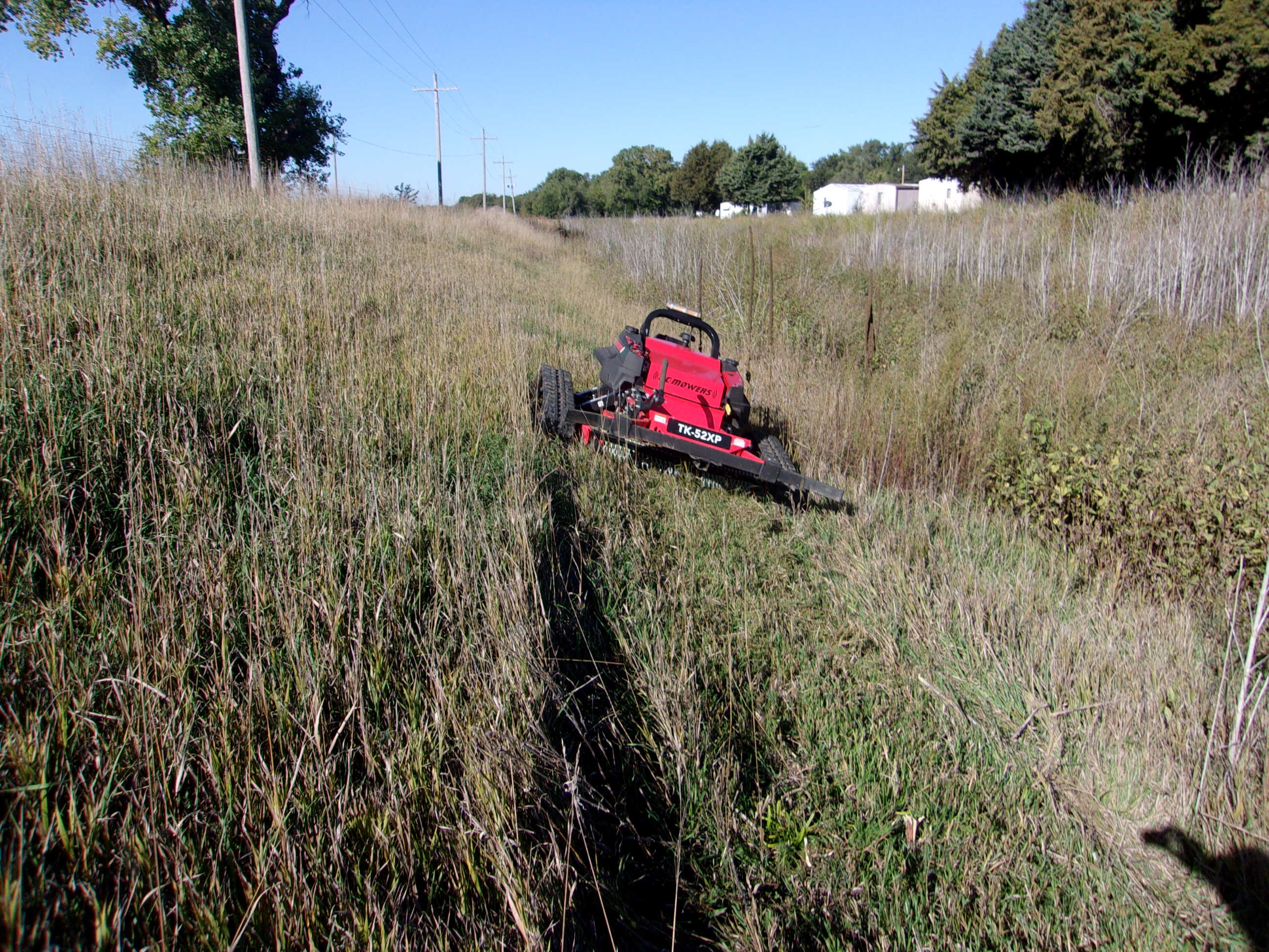 Using a Remote Control Mower to mow on the steep slopes of flood control drainage ditches.